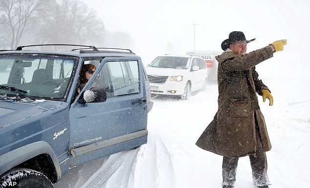 JC Hobbs directs his wife Sarah as they help to pull a van and U-Haul up a hill outside Calhan, Colo