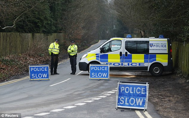 Police officers cordon off the road leading to the tycoon's house near Ascot as they carry out investigations
