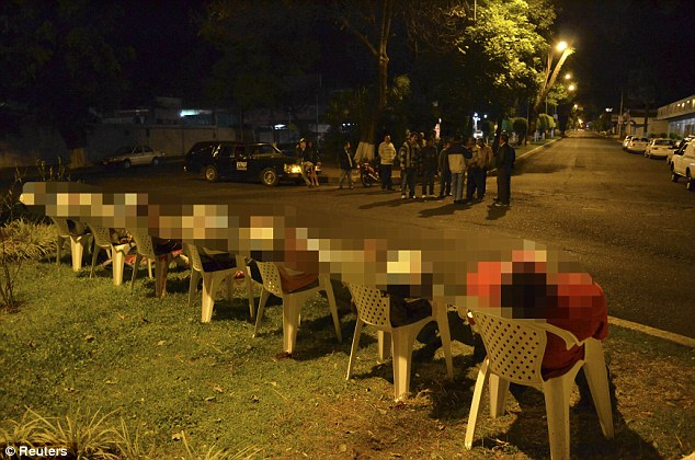 Onlookers: Seven bodies had bullet wounds and had been placed individually in the sitting position