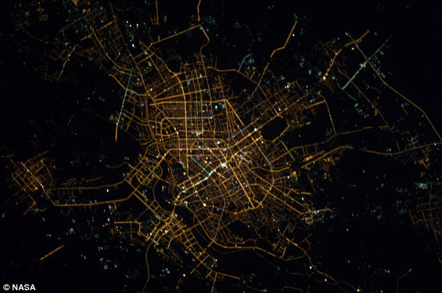 On the grid: Shenyang on China at night with the smaller city of Sujiatun (pictured left)