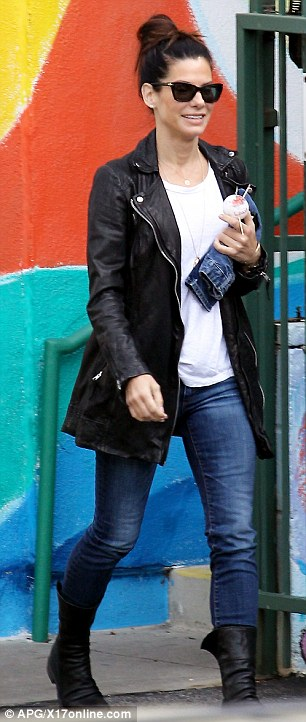 Stylish single: The Blind Side actress looked chic in her leather jacket, denim trousers and lblack boots