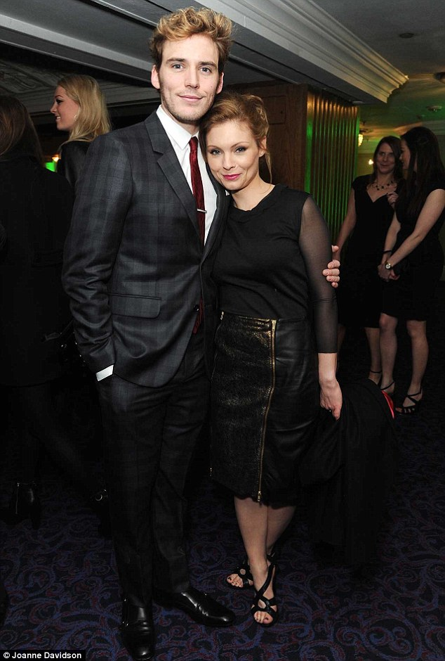 A cause for celebration: Sam Claflin and MyAnna Buring cuddled up inside the venue