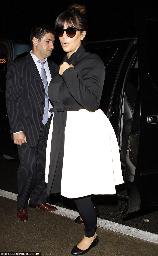 Monochrome maternity wear: Kim Kardashian could not hide her growing pregnancy shape as she jetted out of LAX in a two-toned monochrome coat early on Monday morning