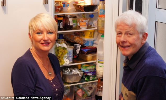 Beverley Cooper (left) screamed when she saw the exotic spider in the fridge starring back at her and after rushing to her aid, husband David (right) caught it in before calling the Scottish SPCA