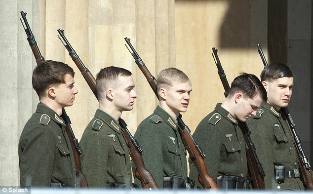 Setting the scene: Castmates who appeared to be dressed as Nazi soldiers were seen marching with guns in the middle of the German city