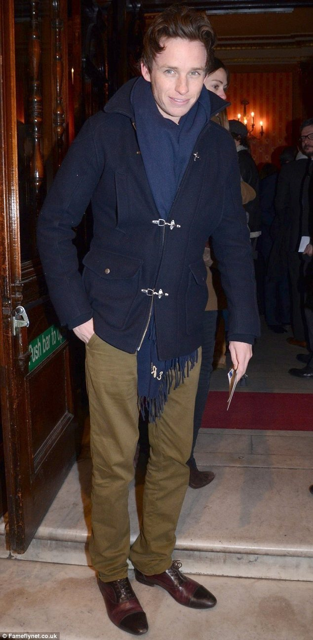 Wrapped up: Eddie Redmayne keeps warm in a duffel coat and blue scarf for the preview night of Peter And Alice