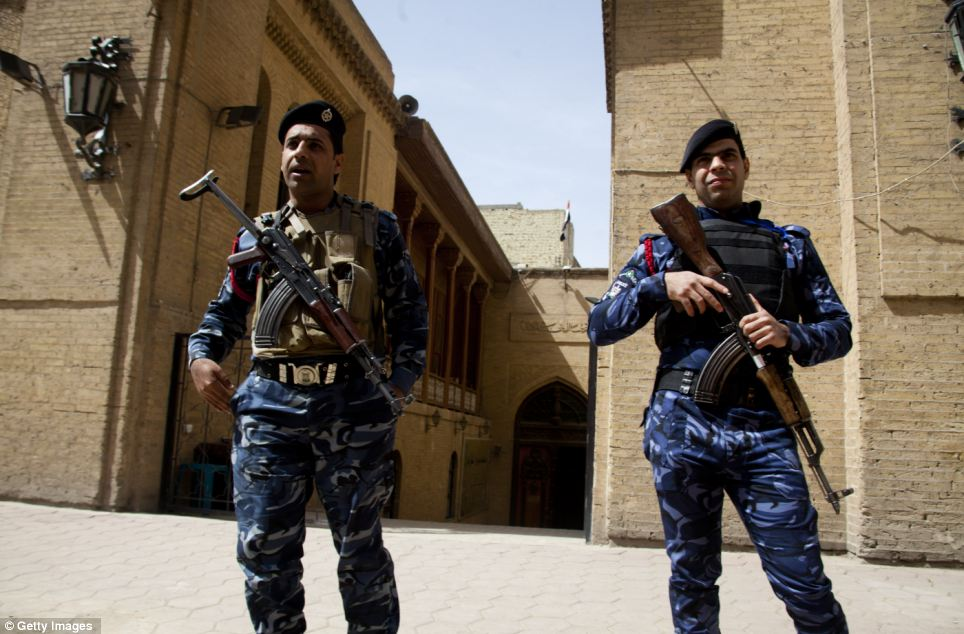 Armed guards: Iraqi policemen guard the entrance to the Baghdad Folklore Museum. The city continues to show the scars of war
