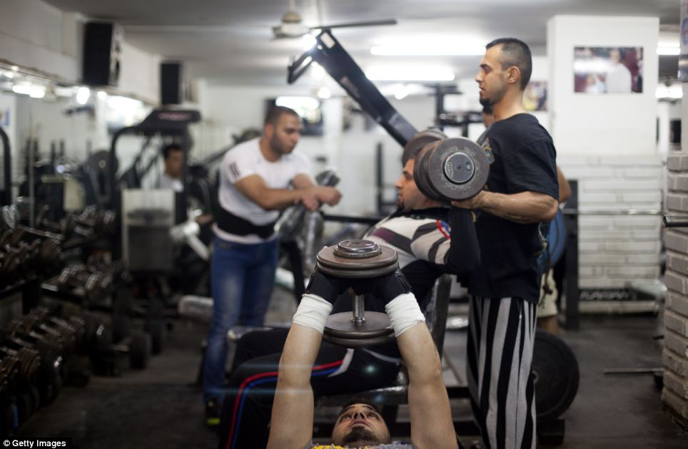 Building up: Hoseen Samer lifts weights in a gym in the affluent Karada district