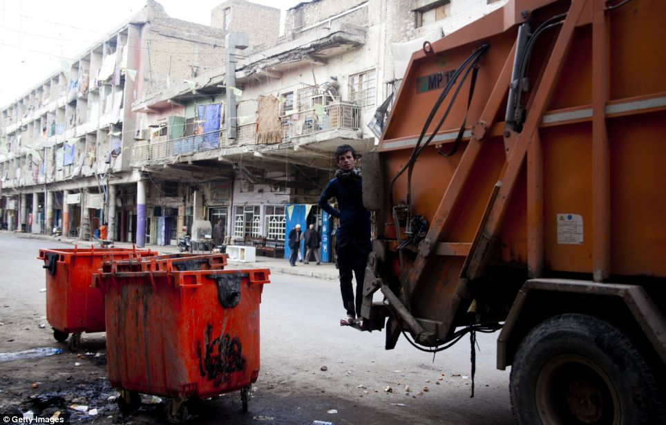 Clean up: A young man collects trash in central Baghdad. Some areas of the city are still said to be lacking services