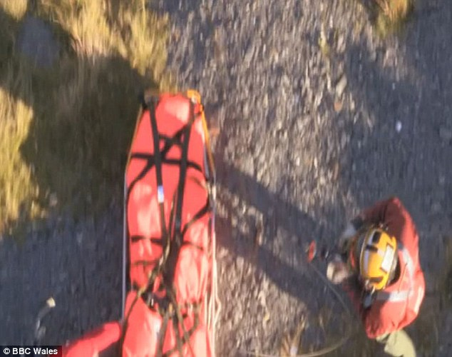 Help: Winchman and paramedic Master Aircrewman Richard Taylor arrives on the ground to administer first aid