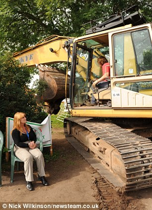 Passive protest: A digger squeezes its way into the field past resident and protester Jane Isham