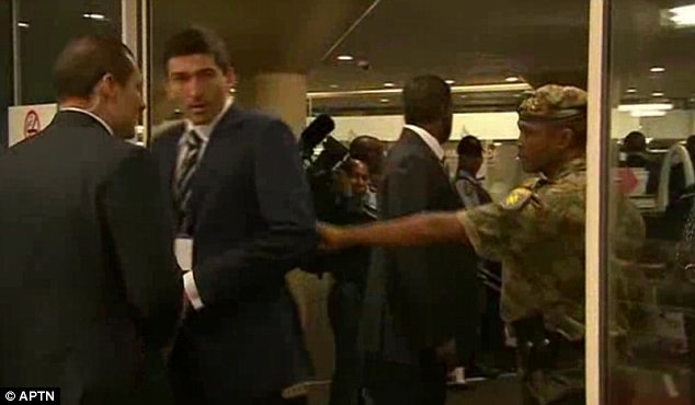 Conflict: A South African security guard pushes Putin's bodyguards out of the convention hall