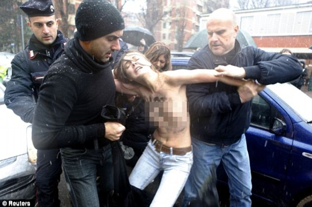 Statement: A FEMEN protester is hauled away during a demonstration at the Italian elections last month