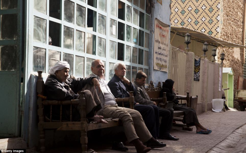 Civilised: These men sit and relax outside a tea room in the Al Fazil area of Baghdad. The image is a stark contrast to the bloody events that these men would have witnessed over the past decade