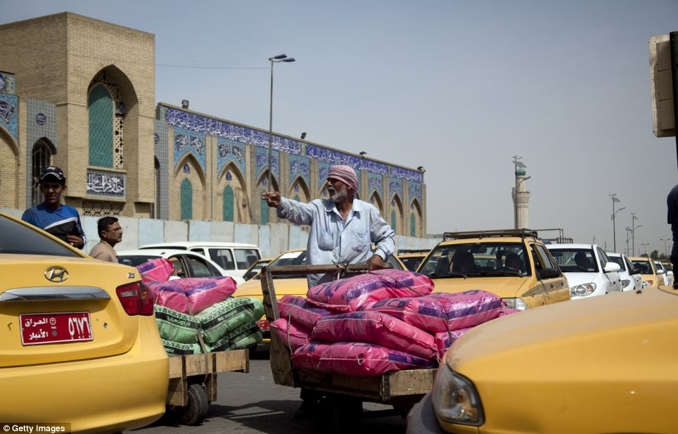 Surviving: Washer Kilani pushes goods through lines of heavy traffic in central Baghdad