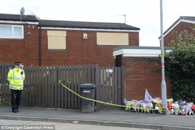 Boarded up: A police officer stands guard next to the home of dog owner Bev Concannon which has been boarded up