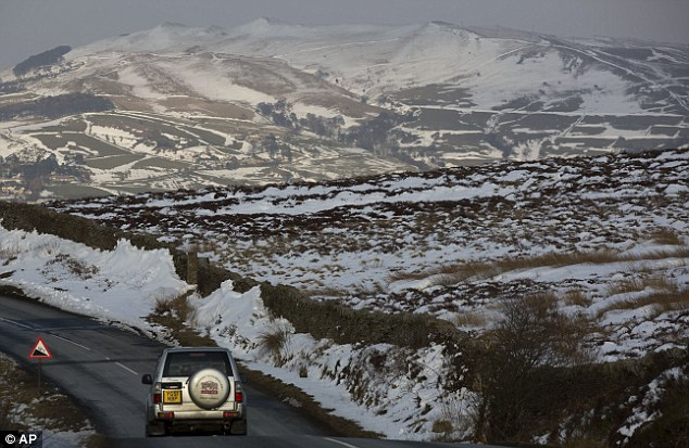 White: A vehicle passes snow drifts near Colne, Lancashire, as Britain continues to shiver in the cold weather