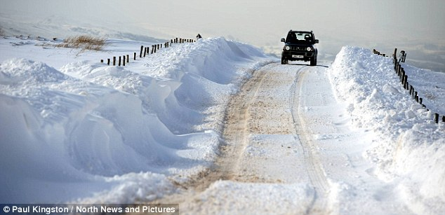 Making way: A driver travels along a snow-lined road near Brough, Cumbria, as Britain braces for a cold Easter