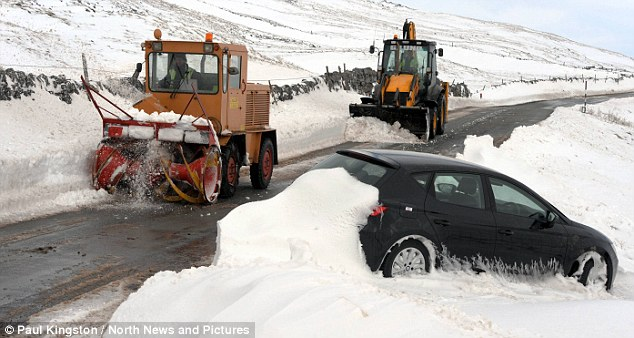 Getting through: A digger and a snow blower clear snow from around a stranded car near Brough, Cumbria