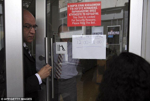 Money grab: A bank employee speaks to a woman outside a closed Laiki branch. The maximum cash withdrawal limit has been set at 300 euros (£250) per day and no checks will be cashed