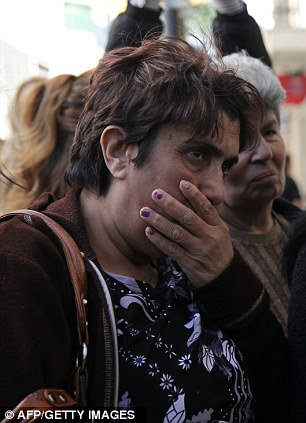 A woman gestures as she waits outside a Laiki bank branch in the old part of the Cypriot capital, Nicosia