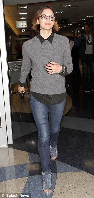 Smash hit: Strutting out of the airport Katharine wore a pair of slim fit denim jeans with a grey jumper