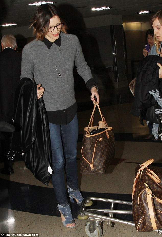 She wears it well: Katharine also travelled in style with designer Louis Vuitton bags
