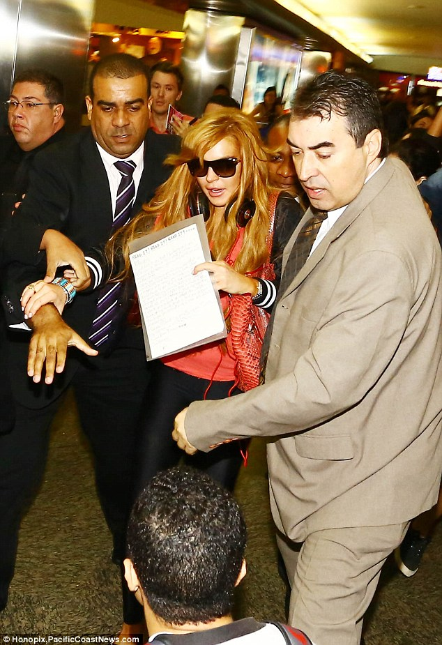 Frenzy: Lindsay Lohan was mobbed by fans as she landed in Brazil on Thursday having jetted in from LA