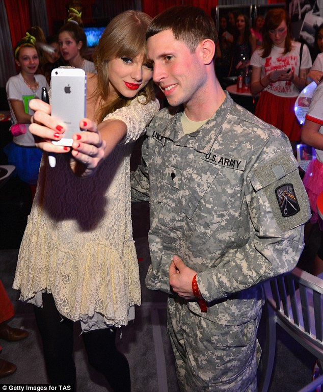 Meet and greet: Taylor Swift took a photograph of herself and a member of the U.S. armed forces backstage at her Club Red experience