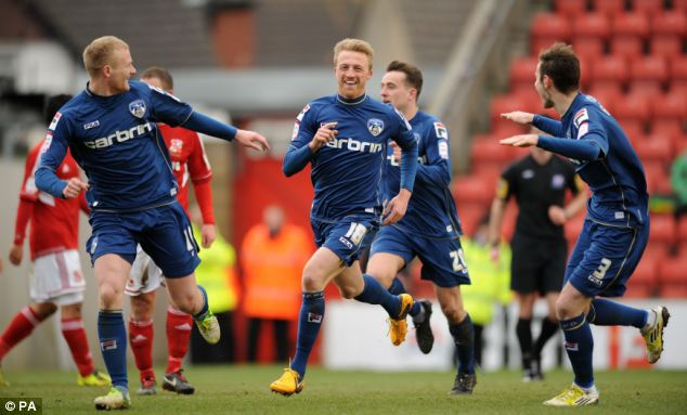 Off the mark: Oldham Athletic's Lee Barnard (centre) scores the opening goal in the 1-1 draw with Swindon