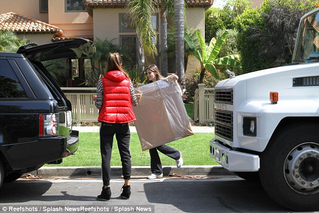 Moral support: Alessandra stands by while her sister, Aline, hoists one of her belongings into a waiting car outside of her Los Angeles home on Thursday