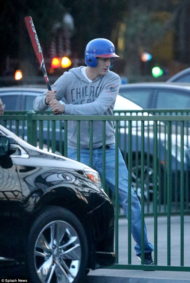 Actor turned coach: Ashton Kutcher instructs a female friend how to play baseball at the Castl Batting Cages in Sherman Oaks, California on Wednesday