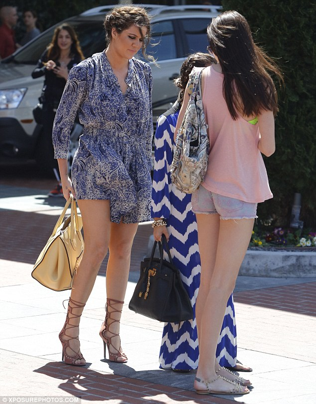 Recovery: Surrounded by her famous sisters, Kourtney and Kendall Jenner, she was seen quickly smoothing the fabric down across her thighs