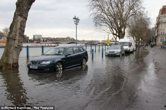 The wheels of parked cars along the riverside were submerged in water after the Thames burst its banks in south west London
