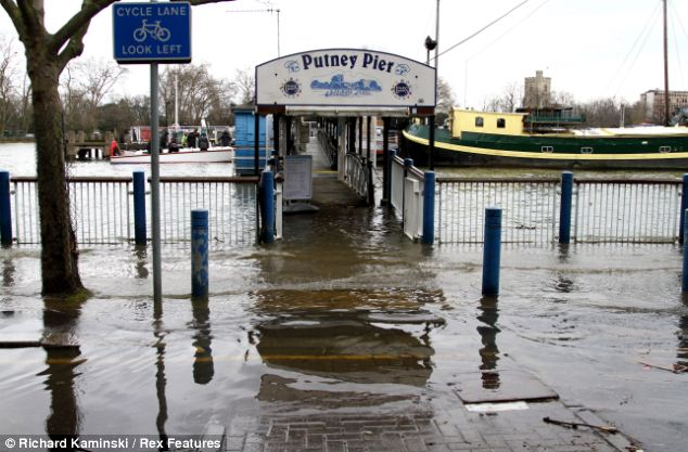 Spring tides and melting snow have caused flooding of the Thames between Barnes and Putney Pier