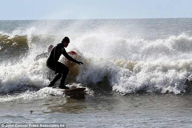 Braving the cold: Despite the freezing temperature this surfer took to the waves in Shoreham near Brighton