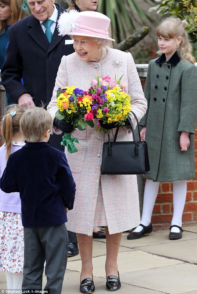 Well-wishers: The Queen receives flowers from children after leaving St George's Chapel in Windsor with her grandchild Lady Louise (pictured right)