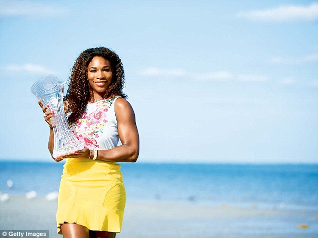 Anything Andy can do: Serena Williams, winner of the women's final at the Sony Open, poses with the trophy at the beach too