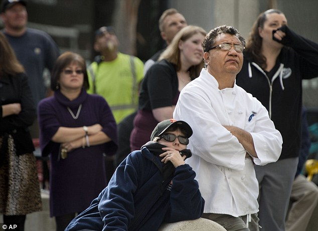 Shocked crowd: People gather near 13th and J streets in Sacramento to watch firefighters as they recover the body of the man who was found hanging from a rope tied to a balcony