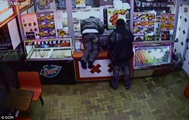 The armed gunman encourages his partner to reach over the counter by slapping his behind