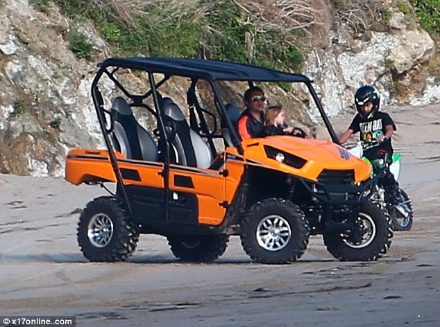 Happy days: With Brad firmly in control he let Knox do a little steering as they raced along the beach