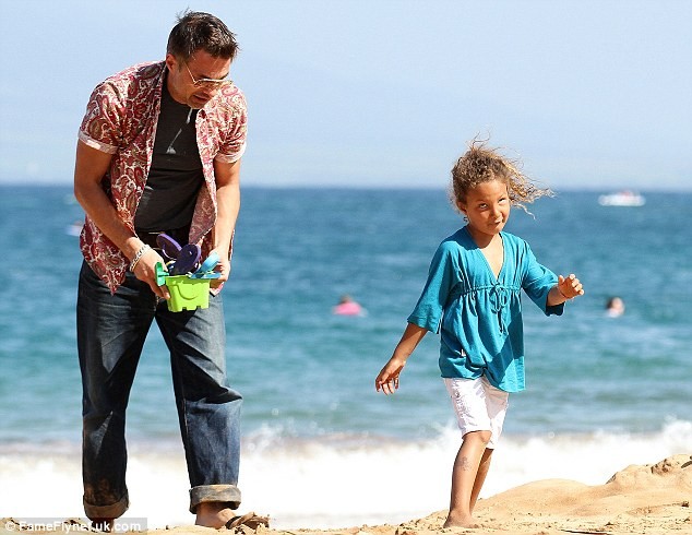 Fun in the sun: Oliver carries Nahla's toys after a day on the beach