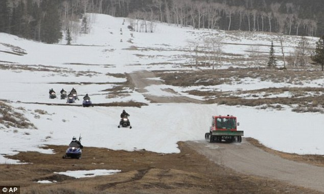 In custody: Snow-mobilers pass the sheriff's truck carrying the 45-year-old suspect
