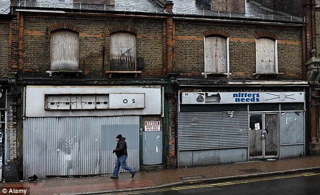 Grim: A man walking past a row of boarded up shops in South Norwood