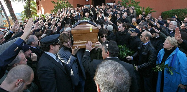 Salute: As the coffin was carried out, those in attendance raise their arms in tribute