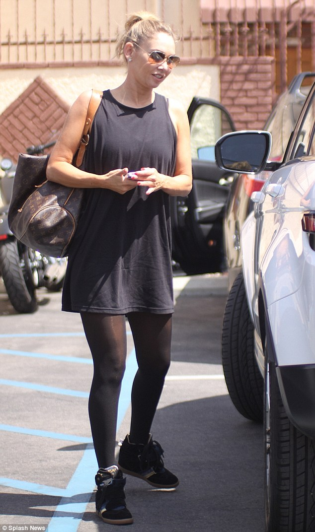 Cute outfit: The dancer showed off her toned physique in a loose-fitting short black dress paired with black stockings