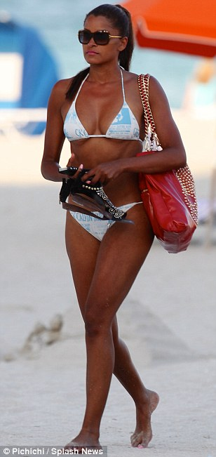 Enough fun for one day: Claudia carried her black strappy sandals as she left the beach after her day of fun in the sun