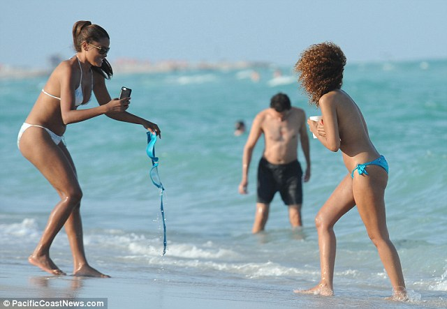 Fooling around: Claudia enjoyed holding her friend's bikini top as she took photographs of her friend
