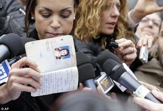 Karima el-Mahroug holds up her passport up to reporters as she is  outside Milan's court house. She denied she was a prostitute and insisted that prosecutors hear her side of the story