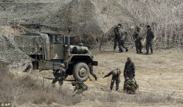 Training: South Korean soldiers place a camouflage net over their vehicle as they take part in training